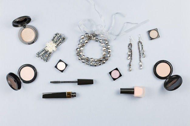 Woman fashion accessories, jewelry and cosmetics on stylish gray background. flat lay