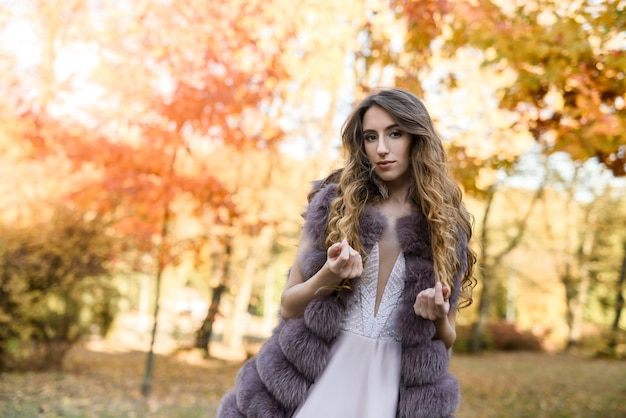 Woman in fashion beige dress and fur coat posing in autumn landscape. trend clothes