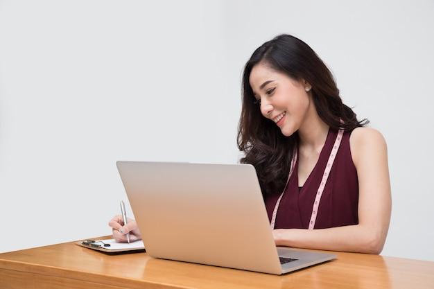 Женщина модельер одежды в красном платье с рулеткой и портативный компьютер изолированы, азиатские женские стильные модели