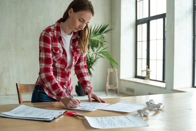 オフィスワークショップで働く女性のファッションデザイナーの手スタイリッシュなファッショニスタの女性は、人々のライフスタイルと職業を仕立てて縫う新しい布のデザインコレクションを作成します