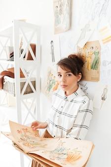 그녀의 스튜디오에 서있는 동안 스케치북을 들고 여자 패션 디자이너