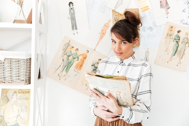 Woman fashion designer holding sketchbook while standing at her studio