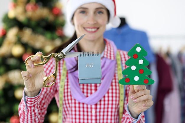 산타클로스 모자를 쓴 여성 패션 디자이너는 패션 트렌드를 위한 달력과 가위를 들고 있다