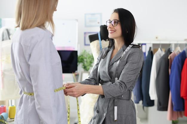Модельер женщина снимает мерки одежды с клиента. концепция пошива одежды ателье