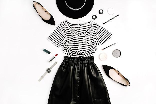 Квартира моды женщины. черная современная одежда и аксессуары. юбка, футболка, шляпа, обувь, помада, часы, пудра на белом фоне. плоская планировка