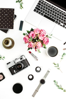 Woman fashion home office desk. workspace with laptop, rose flowers bouquet, retro camera, accessories and cosmetics on white background. flat lay, top view