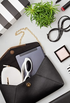 Woman fashion outfit and accessories, handbag, notepad, makeup and earphones in black and white colors. beauty, urban outfit and fashion trends concept. flat lay, top view