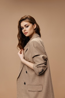 Woman in fashionable coat looking to the side on beige background cropped view