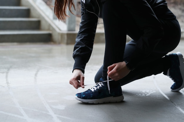A woman fasten her shoelaces. person fastening shoelaces.
