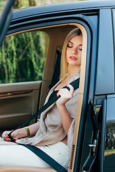 Woman fasten seatbelt in a car