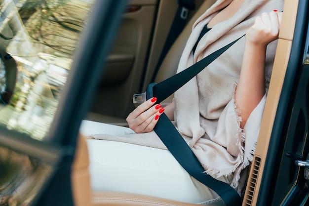 女性がシートベルトを車に固定する