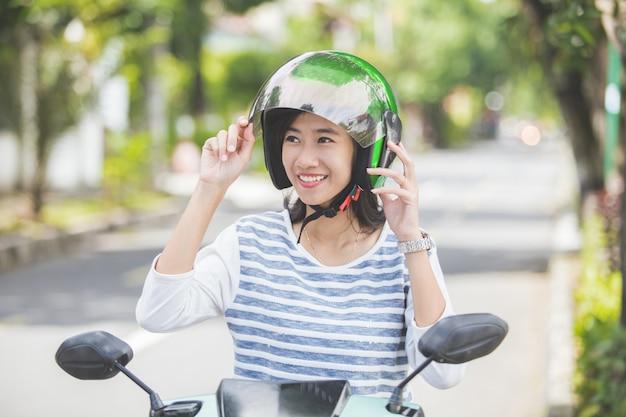 彼女のバイクのヘルメットを締める女性