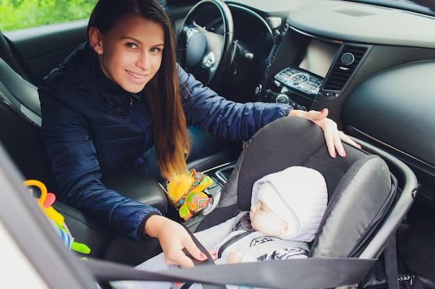 Женщина крепления ее сына на детское сиденье в машине.