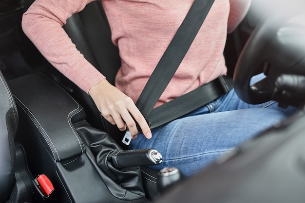 Woman fastening seat belt in car. car safety concept