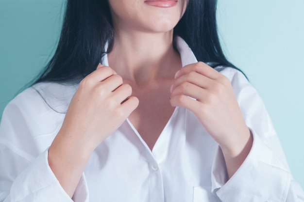 The woman fastens the button of the shirt