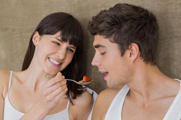 Woman feeding breakfast cereals to man in bedroom
