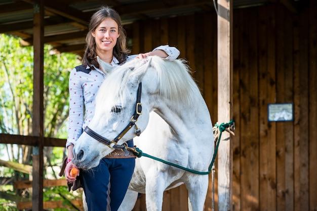 ニンジンを馬に給餌する女性