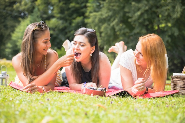 Woman feeding cheery to her friends lying on blanket over the green grass