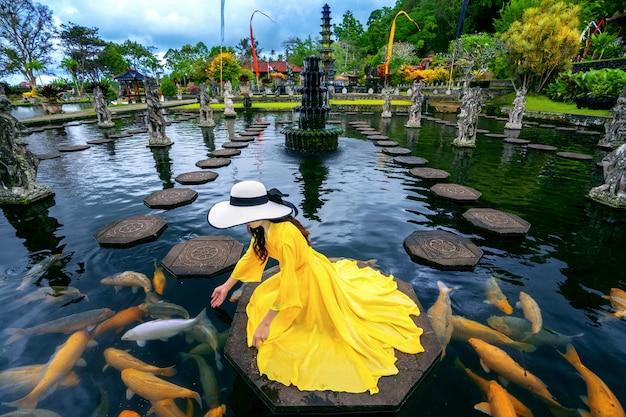 Женщина подавая красочные рыбы в пруде на tirta gangga water palace в бали, индонезия.