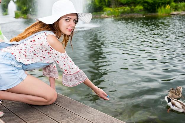 공원의 나무 데크에 무릎을 꿇고 연못에서 오리에게 먹이를 주는 여자