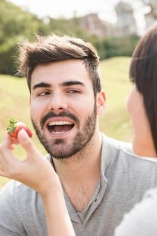 Woman feeding fresh strawberry to her boyfriend
