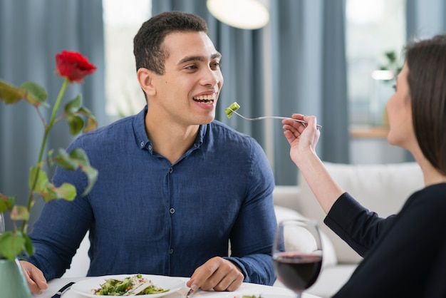 Женщина кормит мужа на романтическом ужине
