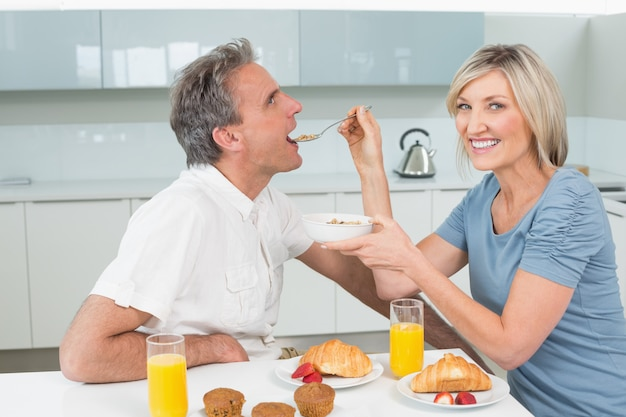 Woman feeding man at breakfast table in kitchen