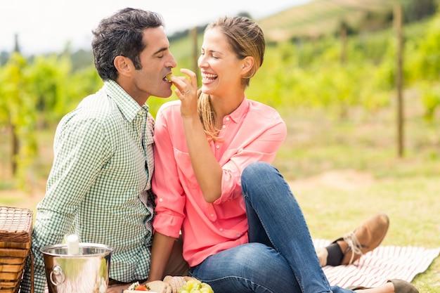 ブドウと男の餌をやる女