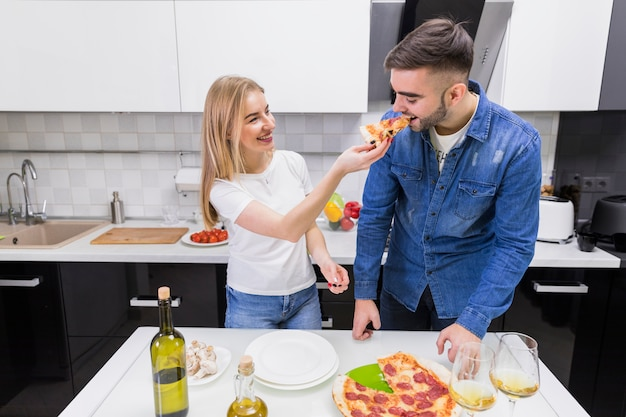 Woman feeding man with pizza in kitchen
