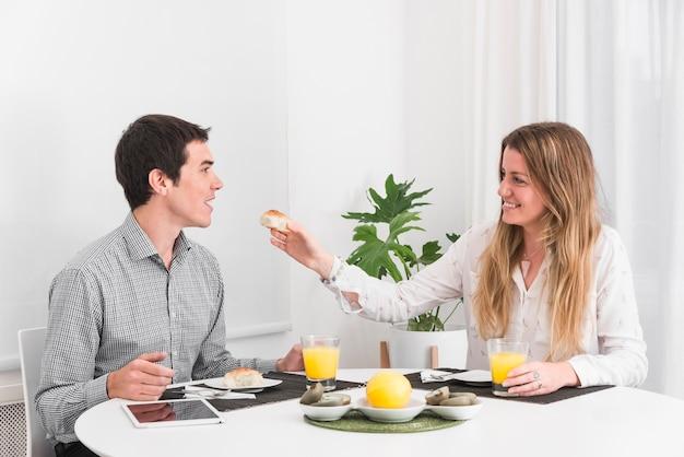 Woman feeding man with small bread