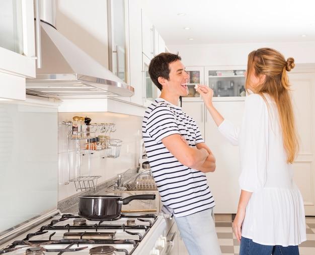 여자는 부엌에서 그녀의 남편에게 팝콘을 먹이