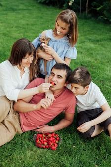 잔디에 그녀의 아이들과 함께 앉아있는 동안 남편에게 딸기를 먹이 여자