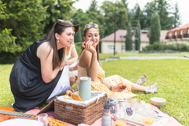 Woman feeding with fork to her friends on picnic