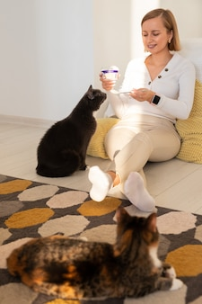 女性は床に座って、スプーンからヨーグルトを猫に与えます。ペットとの家での生活