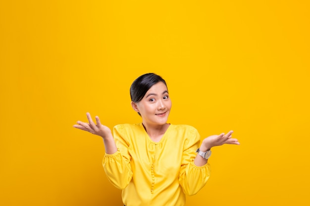 Woman feel confused isolated over yellow wall