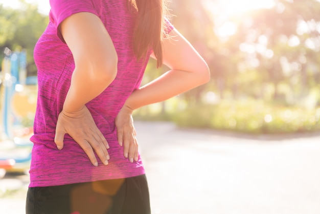 Woman feel pain on her back and hip while exercising, health care concept.
