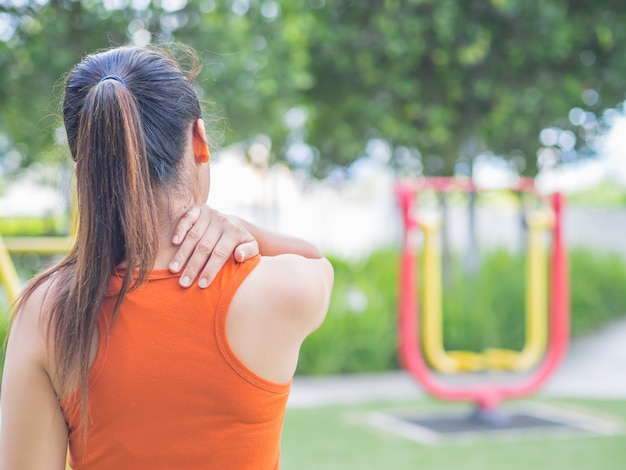 Woman feel pain on her neck and shoulder while exercising, health care concept.