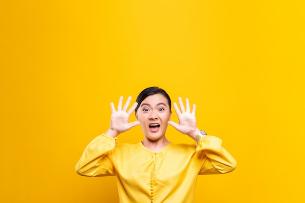 Woman feel scared standing isolated over yellow wall