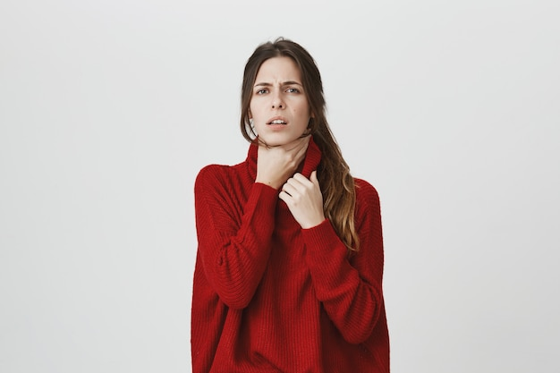 Woman feel sick, touch neck, have sore throat