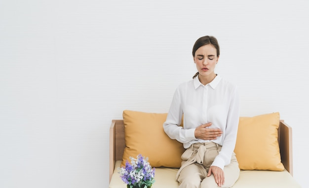 Woman feeling abdominal pain while sitting on sofa at living room