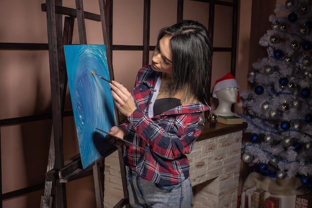 クリスマス休暇中に孤独を感じる女性。絵を描く