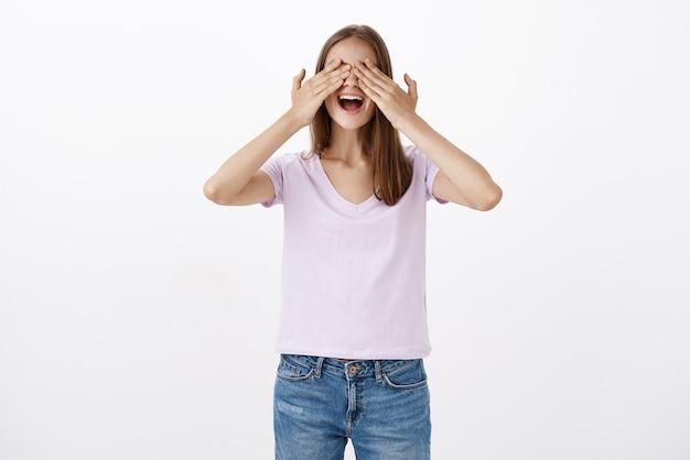 手で目を覆って楽しそうに感じている女性、すごい驚きを待っているカジュアルな終わりに興奮した笑顔