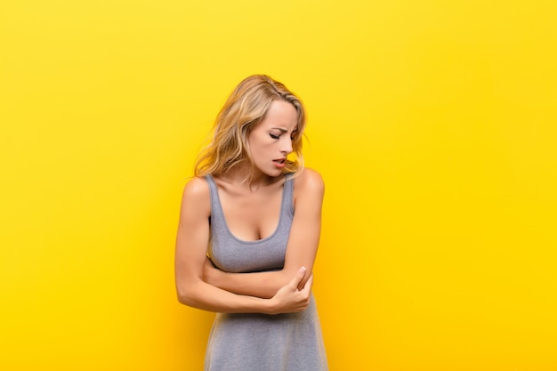 Woman feeling anxious, ill, sick and unhappy, suffering a painful stomach ache or flu