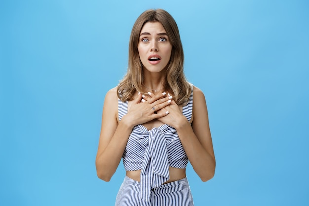 Woman feeling bad for friend empathizing hearing shocking story gasping opening mouth and looking speechless holding palms on breast standing intense and nervous over blue wall.