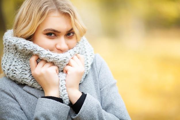 秋の公園で寒さを感じる女性
