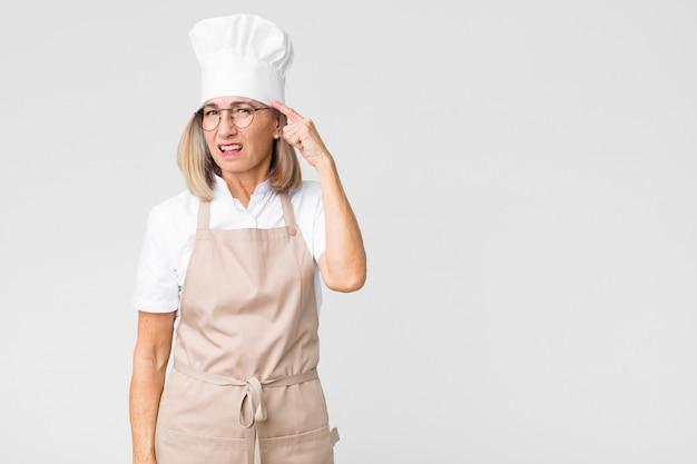 Женщина чувствует себя смущенной и озадаченной, показывая, что вы безумны, сумасшедшие или сошли с ума