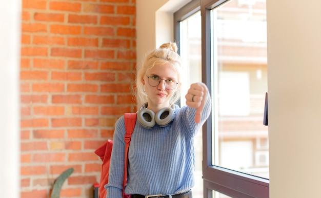 Женщина чувствует себя сердитой, сердитой, раздраженной, разочарованной или недовольной, показывает палец вниз с серьезным взглядом