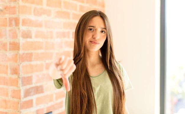 Женщина чувствует себя сердитой, сердитой, раздраженной, разочарованной или недовольной, показывая большой палец вниз с серьезным взглядом