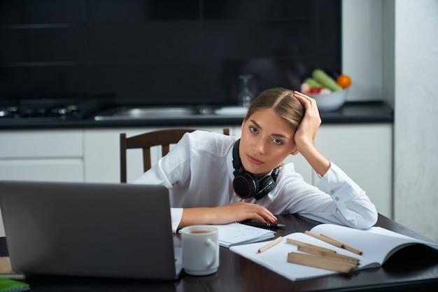 Женщина чувствует себя истощенной после удаленной работы на ноутбуке