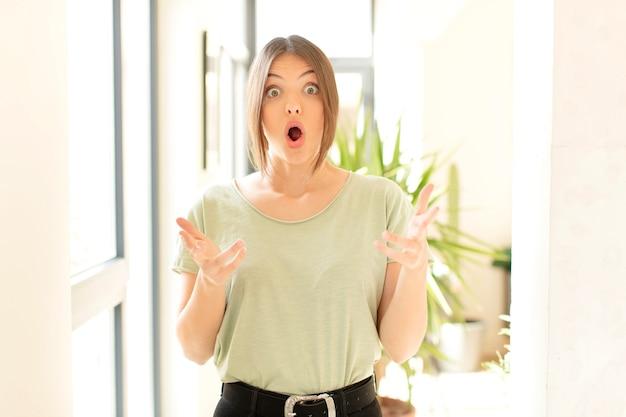 Женщина чувствует себя чрезвычайно шокированной и удивленной, встревоженной и панической, с напряженным и испуганным взглядом